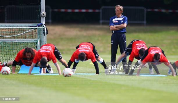 Head coach Christoph Daum watches players warm up during a training session of Eintracht Frankfurt at Commerzbank Arena on May 10, 2011 in Frankfurt...
