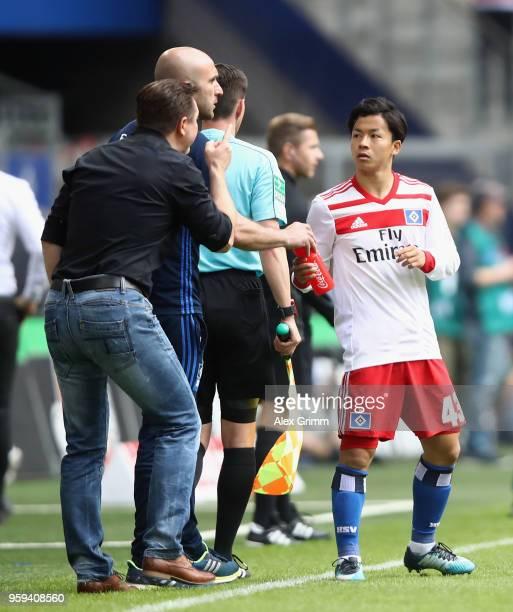 Head coach Chritian Titz of Hamburg talks to Tatsuya Ito during the Bundesliga match between Hamburger SV and Borussia Moenchengladbach at...