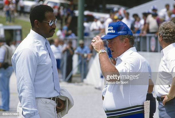 Head Coach Chuck Knox of the Seattle Seahawks talks with Gene Upshaw prior to the start of an NFL football game circa 1983 Knox coached the Seahawks...