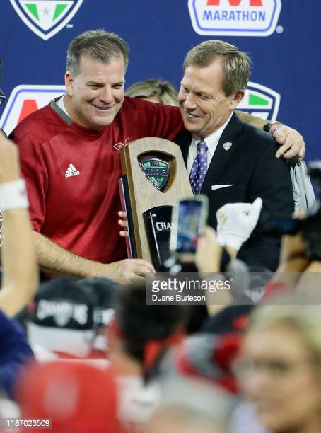 Head coach Chuck Martin of the Miami Redhawks is presented with the 2019 MAC Championship Trophy by Dr Jon Steinbrecher commissioner of the...