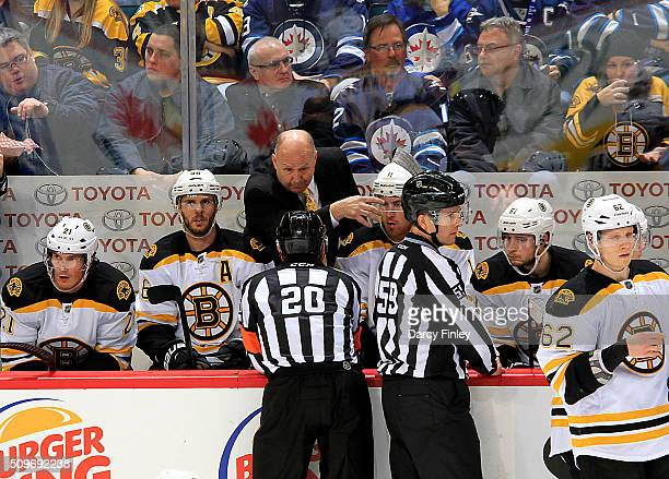 Head Coach Claude Julien of the Boston Bruins argues with referee Tim Peel during a second period stoppage in play against the Winnipeg Jets at the...