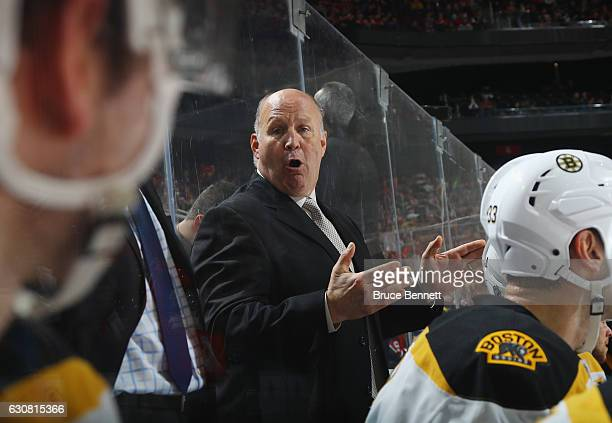 Head coach Claude Julien of the Boston Bruins gives instructions to Brandon Carlo during the second period against the New Jersey Devils at the...