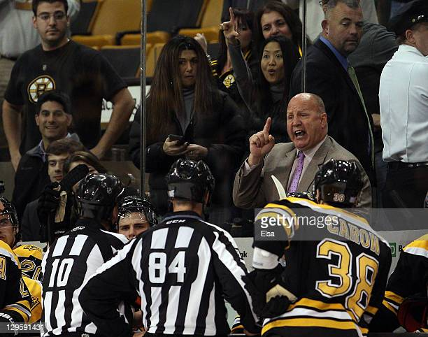 Head coach Claude Julien of the Boston Bruins talks to referee Paul Devorski and linesman Tony Sericolo after Julien was tossed from the game in...
