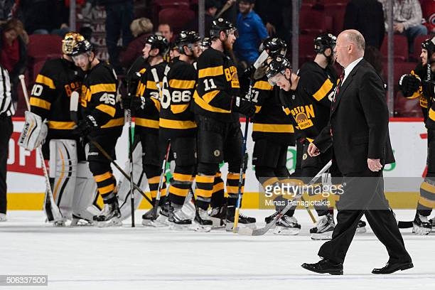 Head coach Claude Julien of the Boston Bruins walks past his team as they celebrate their victory during the NHL game against the Montreal Canadiens...