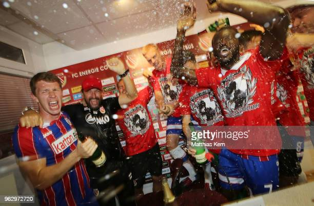 Head coach Claus Dieter Wollitz and his players celebrate after moving up into the third league after the Third League Playoff Leg 2 match between FC...