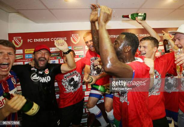 Head coach Claus Dieter Wollitz of Cottbus and his players celebrate after moving up into the third league after the Third League Playoff Leg 2 match...