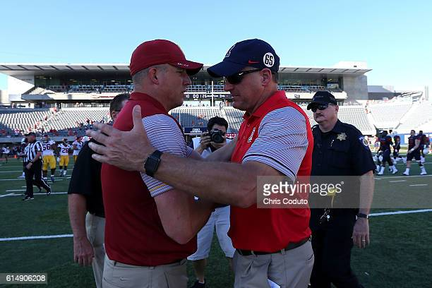Head coach Clay Helton of the USC Trojans and head coach Rich Rodriguez of the Arizona Wildcats shake hands after the college football game at...