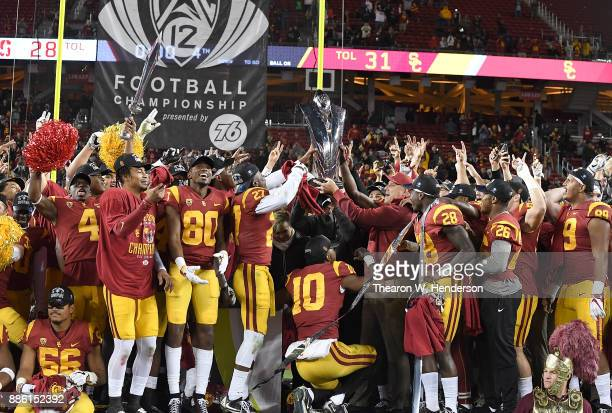Head coach Clay Helton of the USC Trojans holds up the trophy with his team after they beat the Stanford Cardinal 3128 in the Pac12 Football...