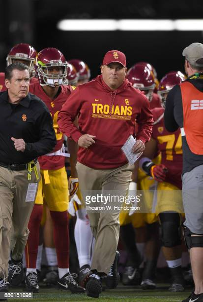 Head coach Clay Helton of the USC Trojans runs onto the field with his team prior to the start of the Pac12 Football Championship Game against the...