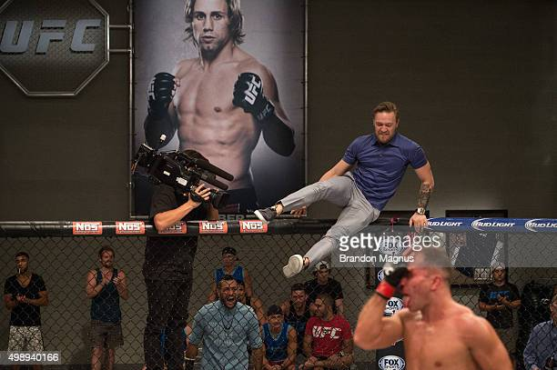 Head coach Conor McGregor jumps into the Octagon after Artem Lobov knocks out Chris Gruetzemacher during the filming of The Ultimate Fighter Team...