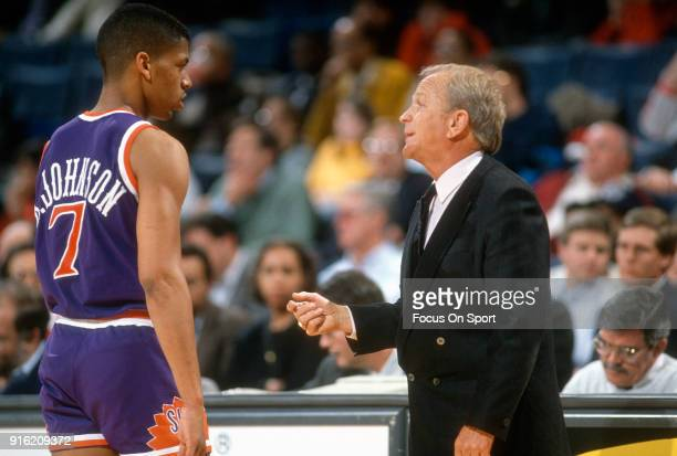 Head coach Cotton Fitzsimmons of the Phoenix Suns talks with his player Kevin Johnson during an NBA basketball game against the Washington Bullets...