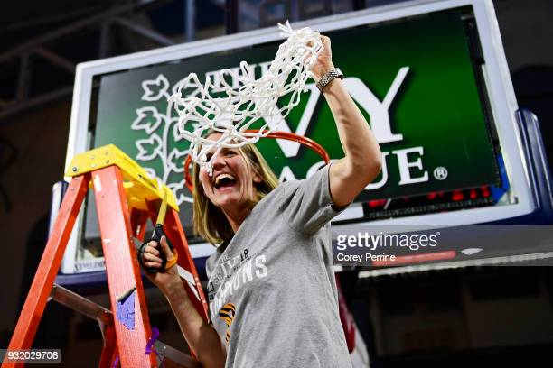 Head coach Courtney Banghart of the Princeton Tigers holds up the netting she cut down after the win at The Palestra on March 11 2018 in Philadelphia...
