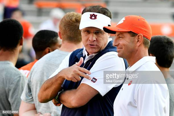 Head coach Dabo Swinney of the Clemson Tigers and head coach Gus Malzahn of the Auburn Tigers talk before the start of the football game at Memorial...