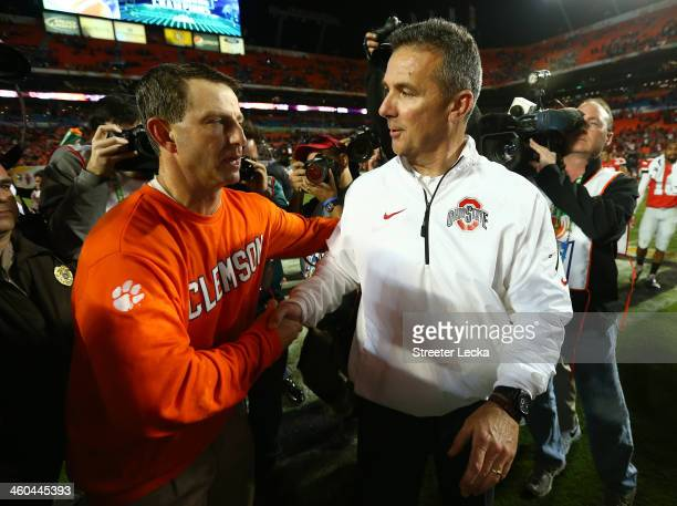Head coach Dabo Swinney of the Clemson Tigers and head coach Urban Meyer of the Ohio State Buckeyes shake hands after the the Discover Orange Bowl at...