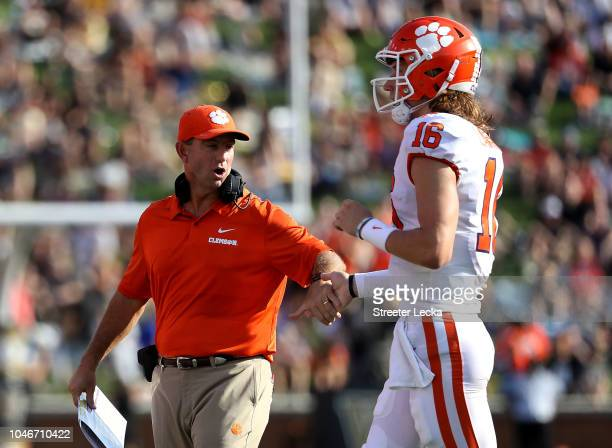 Head coach Dabo Swinney of the Clemson Tigers celebrates a touchdown with Trevor Lawrence of the Clemson Tigers during their game at BBT Field on...