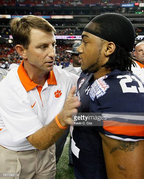 Head coach Dabo Swinney of the Clemson Tigers converses with Tre Mason of the Auburn Tigers after their 26-19 win at Georgia Dome on September 1,...