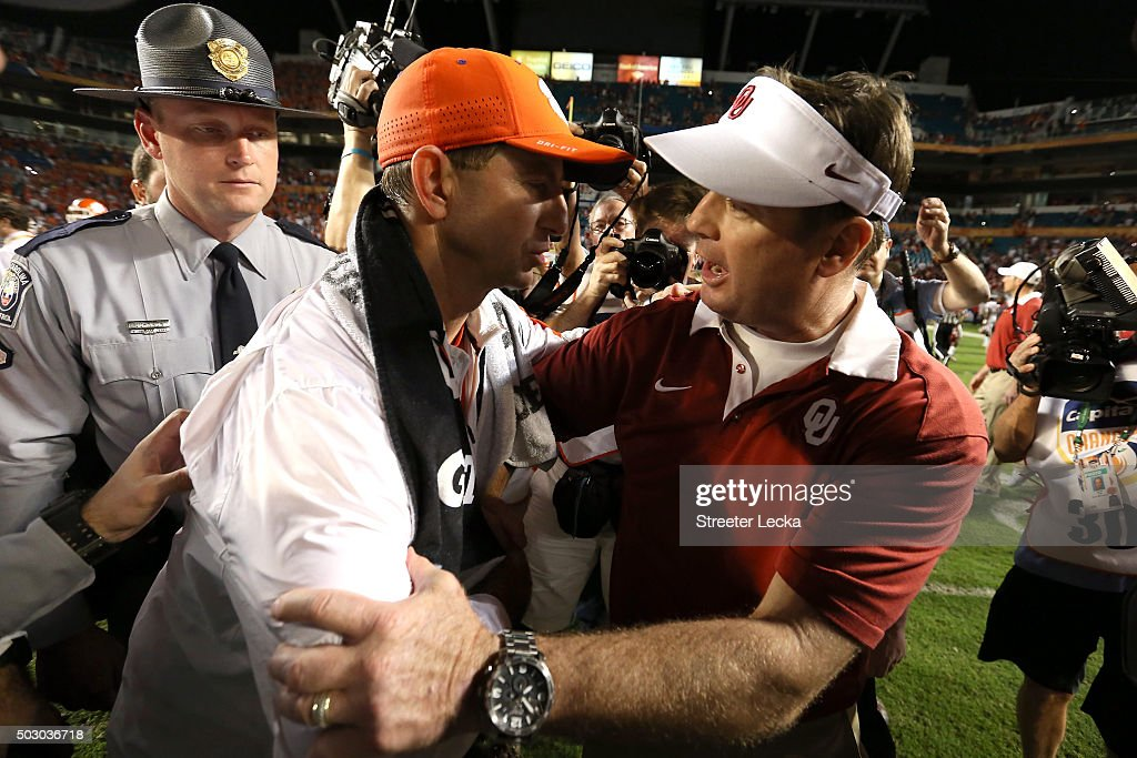 Head coach Dabo Swinney of the Clemson Tigers greets head coach Bob Stoops of the Oklahoma Sooners after the Clemson Tigers defeat the Oklahoma Sooners with a score of 37 to 17 to win the 2015 Capital One Orange Bowl at Sun Life Stadium on December 31, 2015 in Miami Gardens, Florida.