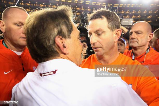 Head coach Dabo Swinney of the Clemson Tigers meets head coach Nick Saban of the Alabama Crimson Tide at midfield after his 4416 win in the CFP...