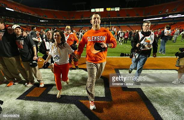Head coach Dabo Swinney of the Clemson Tigers runs off the field with Kathleen Swinney after defeating the Ohio State Buckeyes during the Discover...