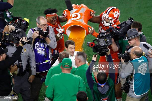 Head coach Dabo Swinney of the Clemson Tigers shakes hands with head coach Brian Kelly of the Notre Dame Fighting Irish as his players dump Gatorade...