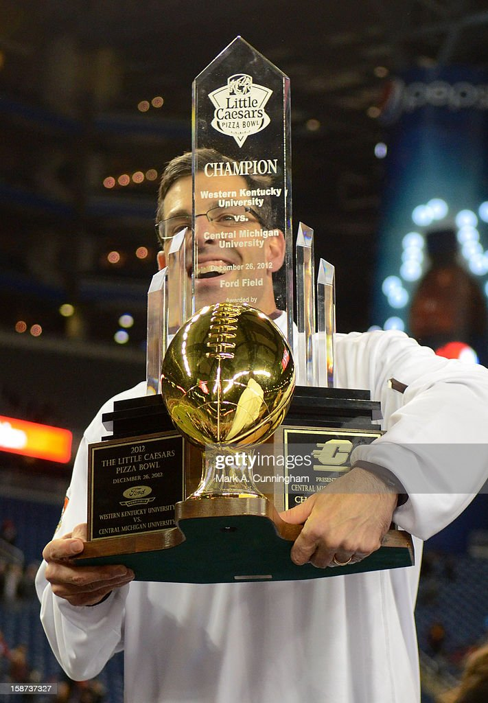 Head Coach Dan Enos of the Central Michigan University Chippewas holds up the Little Caesars Pizza Bowl Championship Trophy after the victory against the Western Kentucky University Hilltoppers at Ford Field on December 26, 2012 in Detroit, Michigan. The Chippewas defeated the Hilltoppers 24-21.
