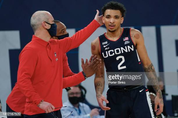 Head coach Dan Hurley of the Connecticut Huskies and assistant coach Kimani Young give encouragement to James Bouknight during the semifinal game...