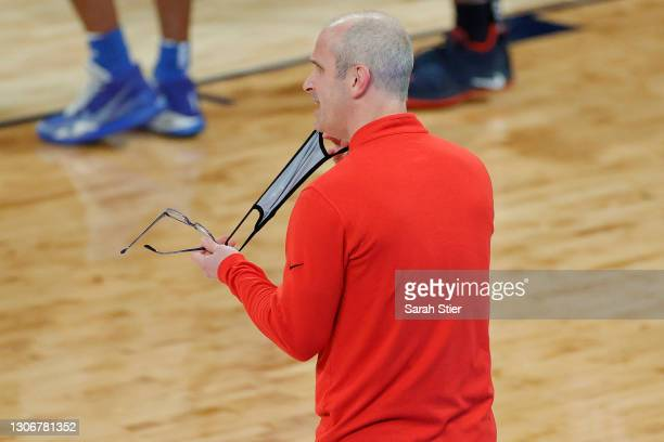 Head coach Dan Hurley of the Connecticut Huskies removes his mask as he questions a call in the first half against the Creighton Bluejays during the...