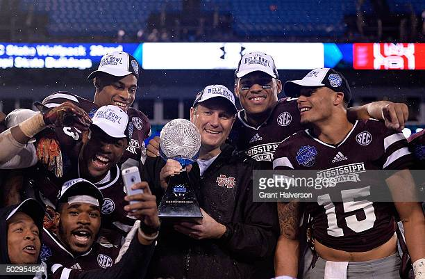 Head coach Dan Mullen and the Mississippi State Bulldogs celebrate with the trophy after a win over the North Carolina State Wolfpack during the Belk...