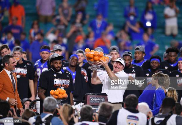 Head Coach Dan Mullen of the Florida Gators raises the Orange Bowl Trophy after winning the Capital One Orange Bowl against the Virginia Cavaliers at...