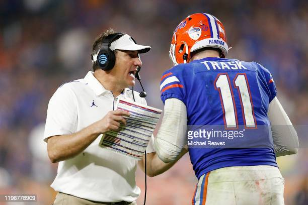 Head coach Dan Mullen of the Florida Gators talks with Kyle Trask against the Virginia Cavaliers during the second half of the Capital One Orange...