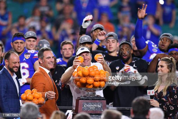 Head Coach Dan Mullen of the Florida Gators throws oranges to the players after winning the Capital One Orange Bowl against the Virginia Cavaliers at...