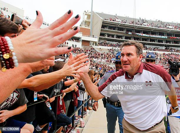 Head coach Dan Mullen of the Mississippi State Bulldogs celebrates with fans after the end of an NCAA college football game at Davis Wade Stadium on...