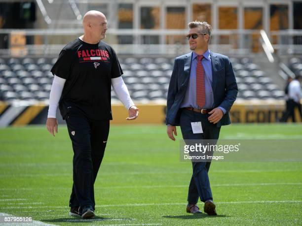 Head coach Dan Quinn and general manager Thomas Dimitroff of the Atlanta Falcons converse as they walk onto the field prior to a preseason game on...