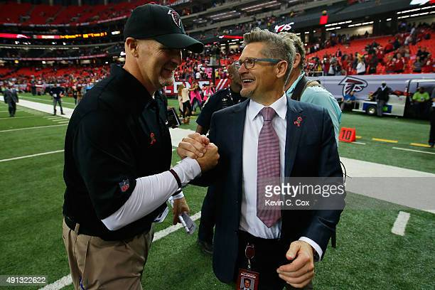 Head coach Dan Quinn of the Atlanta Falcons celebrates with general manager Thmoas Dimitroff after beating the Houston Texans at the Georgia Dome on...