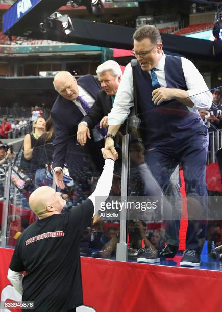 Head coach Dan Quinn of the Atlanta Falcons shakes hands with tv personalities Terry Bradshaw Jimmy Johnson and Howie Long during Super Bowl 51 at...