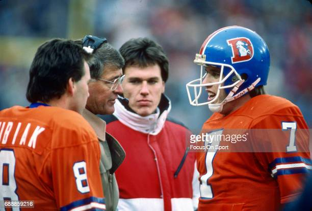 Head Coach Dan Reeves of the Denver Broncos talks with quarterback John Elway on from the sidelines during an NFL football game circa 1983 at Mile...