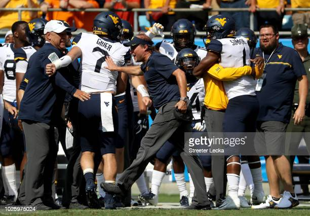 Head coach Dana Holgorsen celebrates on the sidelines with Will Grier of the West Virginia Mountaineers after a touchdown during their game against...