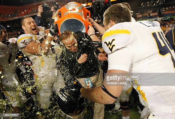 Head coach Dana Holgorsen of the West Virginia Mountaineers has gatorade dumped on his head by his players including Tyler Rader of the West Virginia...