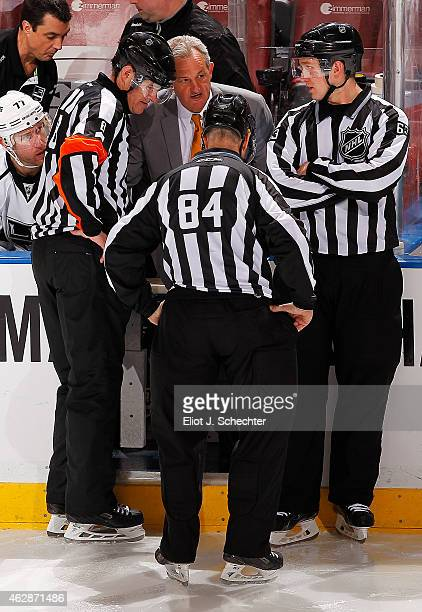 Head Coach Darryl Sutter of the Los Angeles Kings chats with NHL on ice officials during a break in the action against the Florida Panthers at the...