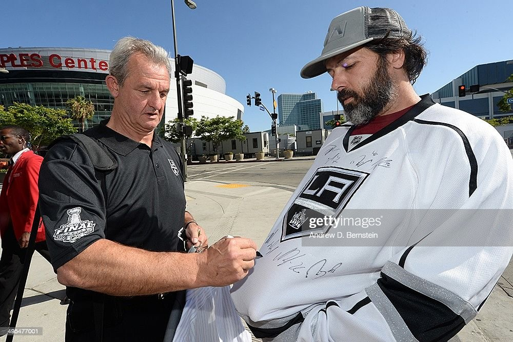 Head coach Darryl Sutter of the Los Angeles Kings signs an autograph as he walks across the street away from Staples Center after the 2014 NHL Stanley Cup Final Media Day on June 3, 2014 in Los Angeles, California.