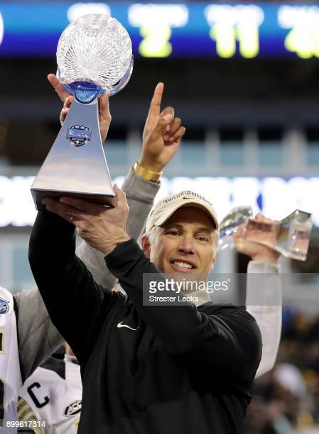 Head coach Dave Clawson of the Wake Forest Demon Deacons celebrates with the trophy after defeating the Texas AM Aggies 5552 after the Belk Bowl at...
