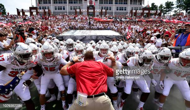 Head coach Dave Doeren and the North Carolina State Wolfpack take the field for their game against the Georgia State Panthers at Carter-Finley...