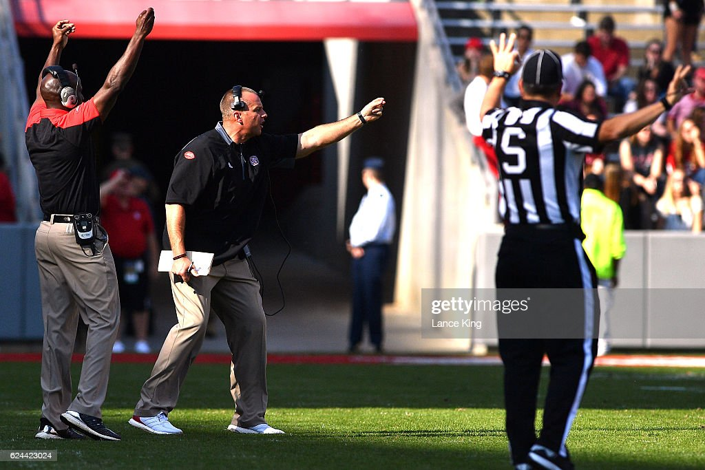 Head coach Dave Doeren (C) of the North Carolina State Wolfpack directs his team during their game against the Miami Hurricanes at Carter-Finley Stadium on November 19, 2016 in Raleigh, North Carolina.