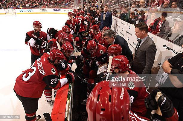 Head coach Dave Tippett of the Arizona Coyotes draws up a play for his players on the bench against the Dallas Stars at Gila River Arena on December...