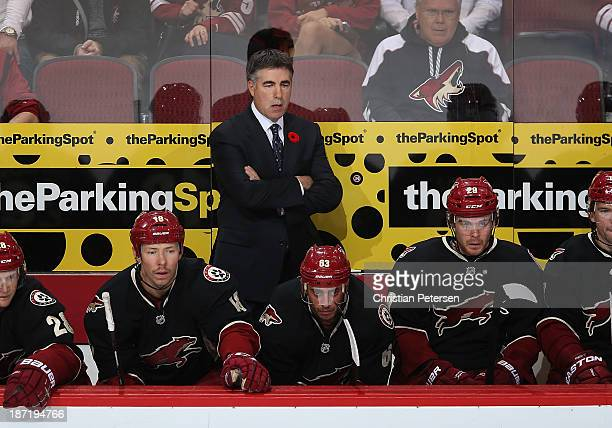 Head coach Dave Tippett of the Phoenix Coyotes watches from the bench during the NHL game against the Vancouver Canucks at Jobingcom Arena on...