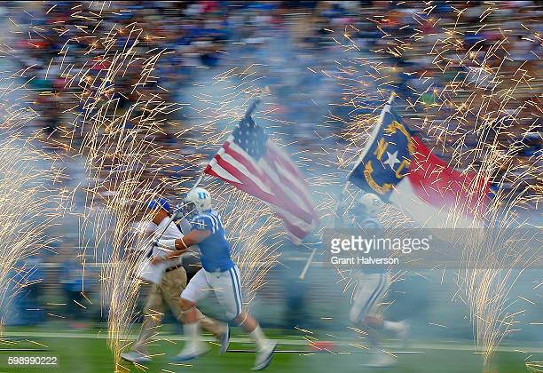Head coach David Cutcliffe and Dominic McDonald of the Duke Blue Devils lead the team onto the field for their game against the North Carolina...