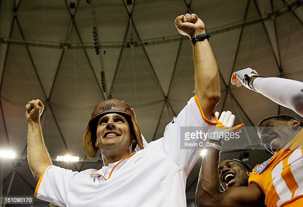 Head coach Derek Dooley of the Tennessee Volunteers celebrates with the leather helmet after their 35-21 over the North Carolina State Wolfpack at...