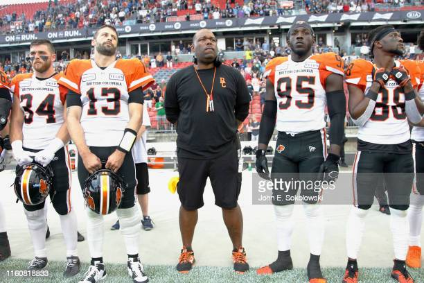 Head coach DeVone Claybrooks with David Mackie and Mike Reilly and Darius Allen and Shaq Johnson of the BC Lions during the anthem before a game...