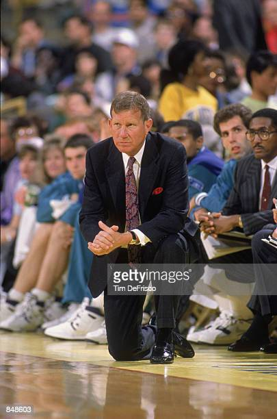 Head coach Dick Harter of the Charlotte Hornets kneels on the sideline during an NBA game at Charlotte Colesium in 1989