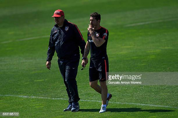 Head coach Diego Pablo Simeone of Atletico de Madrid speaks with assistant coach German Burgos during the training session during the Club Atletico...